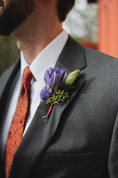 purple flower orange ribbon boutonniere